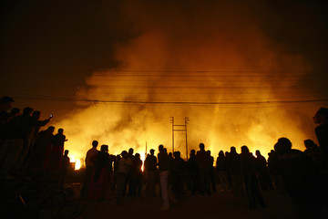Nepalese people watch the fire caught at the grassland and bushes adjoining Tribhuvan International Airport in Kathmandu