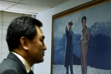 A paint of former leader Kim Jong-il and former president Kim Il-sung is seen while North Korea's new deputy U.N. ambassador An Myong Hun exits the room after speaking to the media in New York