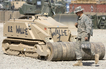 U.S. Army soldier walks past a de-mining robot at Camp Leatherneck in Helmand province, southern Afghanistan