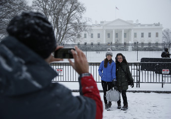 People pose for pictures in the freshly fallen snow outside the White House after snowstorm arrived in Washington