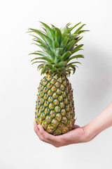 Male hand holding a pineapple isolated on white.
