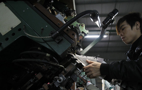 A man works on an assembly line at a shoe factory in Tan Lap village