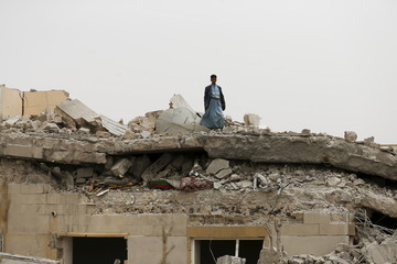 Guard stands on the collapsed roof of the house of General Ali al-Dhafif, a Yemeni army brigade commander, after it was hit by Saudi-led air strikes near Sanaa, Yemen