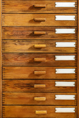 Vintage wooden drawers with empty enamel labels