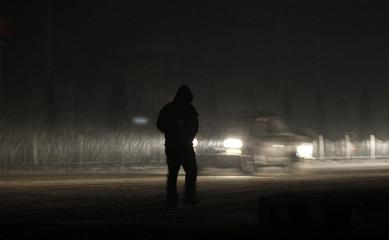 A Kashmiri man walks during a snowfall in Srinagar