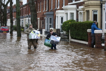 Rescue workers are seen helping locals during flooding caused by heavy rainfall in the Warwick Road area of Carlisle, Britain
