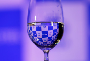 A Tata Steel logo is seen through a glass of water at a news conference announcing the fourth quarter results of the company in Mumbai