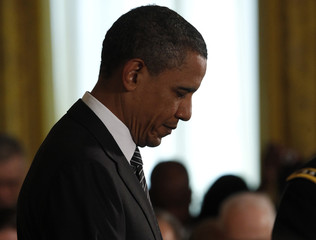 U.S. President Barack Obama bows his head during the invocation of a ceremony held to posthumously award the Medal of Honor