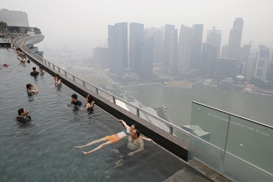 People swim in an infinity pool overlooking the skyline of the central business district shrouded by haze in Singapore