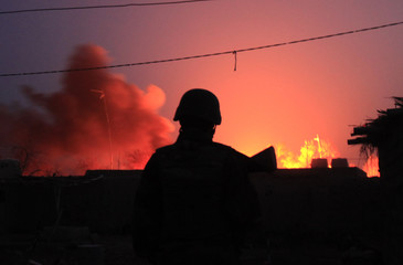 An Afghan soldier stands in front of burning gas storage set on fire by Taliban fighters in town of Marjah in Nad Ali district of Helmand province