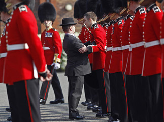 A member of the Irish Guards is supported after feeling unwell during an inspection at their barracks in Windsor, southern England
