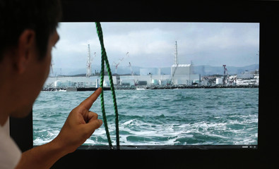 Associate Professor Thornton points at video of Fukushima nuclear plant in Tokyo