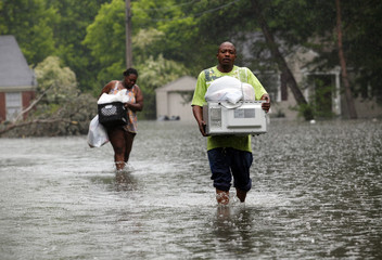 Jonathan White and Leandra Felton wade through slowly rising floodwaters with items from their home in Memphis