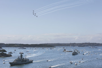 RAAF Roulettes aerobatics team performs a flypast as RAN warship HMAS Perth enters Sydney Harbour as part of the International Fleet Review celebrations