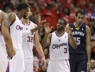 Clippers point guard Chris Paul slaps hands with teammates Blake Griffin and DeAndre Jordan during their NBA game against the Grizzlies in Los Angeles