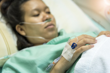 Patient Asian Pregnant Woman drip receiving a saline solution and oxygenation on the bed before delivery