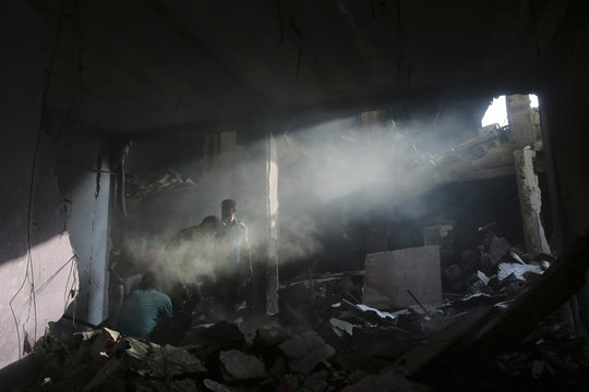 A beam of light illuminates smoke as Palestinians inspect the remains of a commercial center, which witnesses said was hit by an Israeli air strike on Saturday, in Rafah