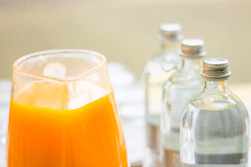 Mineral water bottles and a glass pitcher of orange juice, ready for buffet or catering event.