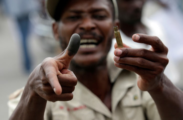 A supporter of Fanmi Lavalas political party shows the case of a bullet shot in the air by a member of the General Security Unit of the National Palace (USGPN) to disperse them as they marched next to the National Palace of Port-au-Prince, Haiti