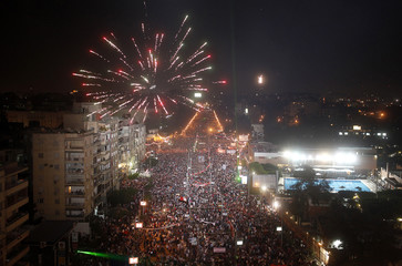 Fireworks explode in the sky as protesters gather for a mass demonstration to support the army in front of the presidential palace in Cairo