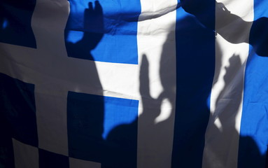 The silhouette of a woman applauding is seen on a Greece flag during a pro-Greece protest in Barcelona