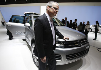 Jacoby, CEO of Volkswagen Group of America, leans on the Touareg Hybrid as he talks to reporters at the New York International Auto Show in New York