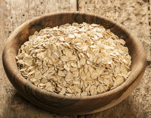 Plate with raw oatmeal on wooden table.