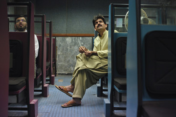 Stockbrokers sit while they monitor stock prices on a computer screen during a trading session at the Karachi Stock Exchange