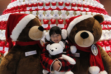 A girl poses for photographs in front of a Christmas tree decorated with Teddy bears during a promotional charity event for the upcoming Christmas holiday season at Grand Intercontinental Seoul Parnas Hotel in Seoul