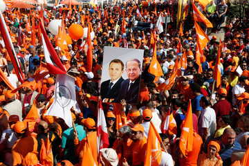 Supporters of the Free Patriotic Movement (FPM) carry flags and a picture of Christian politician and FPM founder Michel Aoun with Lebanese Foreign Minister and head of the Free Patriotic Movement (FPM) Gebran Bassil