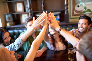 friends drinking beer and making high five at bar