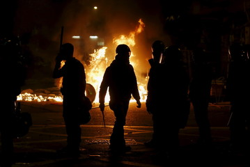 A riot policeman walks in front of a fire set by protesters at a junction in Mongkok district in Hong Kong