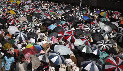 Anti-government protesters shelter themselves with umbrellas during a rally to demand the trial of Yemen's outgoing President Ali Abdullah Saleh, in Sanaa