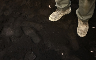 A worker of the Public Power Corporation stands on coal dust during a rally outside Greece's Environment Ministry in Athens