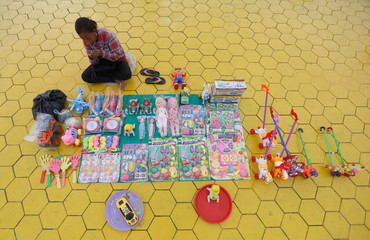 A girl sells toys in front of the Royal Palace in Phnom Penh