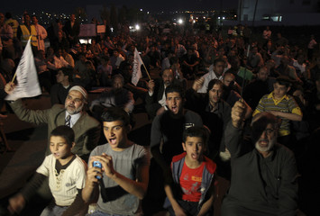 Syrian refugees join Jordanian activists and shout slogans against Syria's President Assad during a demonstration in Amman