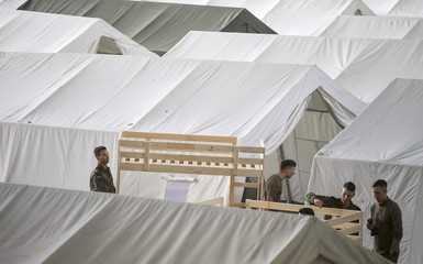 German armed forces Bundeswehr soldiers set up tents and beds for migrants in a hangar of the former Tempelhof airport in Berlin