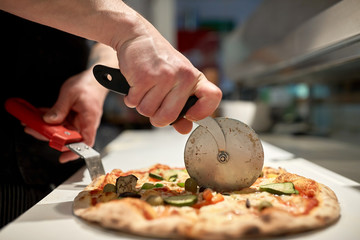 Tuinposter Pizzeria cook cutting pizza to pieces at pizzeria