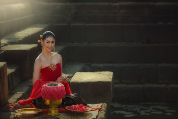 Asian beautiful Thai woman sitting in red dress on stone pagoda of culture cambodia style in Thailand