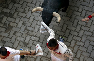 Runners lead a Conde de la Maza fighting bull at the entrance to the bullring during the sixth running of the bulls of the San Fermin festival in Pamplona