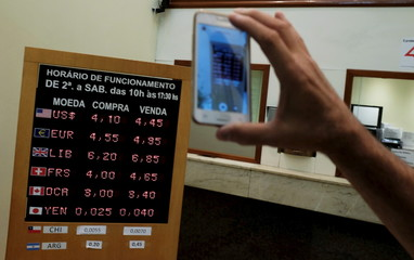 Man takes a picture of a board showing the Real-U.S. dollar and several foreign currencies exchange rates in Sao Paulo