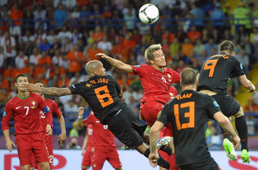 Portugal's Fabio Coentrao jumps for the ball sorrounded by Netherlands' Nigel de Jong, Ron Vlaar and Klaas-Jan Huntelaar during their Group B Euro 2012 soccer match in Kharkiv