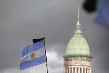 A black ribbon is seen on a national flag with the National Congress building in the background during a silent march to honour late state investigator Alberto Nisman in Buenos Aires