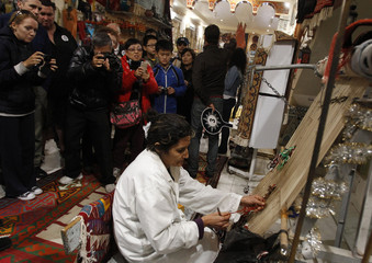 Tourists take pictures of a woman weaving a carpet in the medina, the old city of Tunis