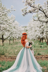 Young red-haired woman in a luxurious dress is standing in a blooming garden