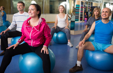 mature men and women involved in sports gym