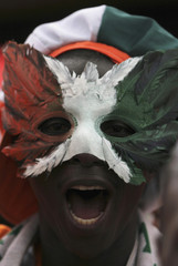 An Ivory Coast fan, wearing a mask in the colours of the Ivory Coast national flag, cheers in a street in Malabo