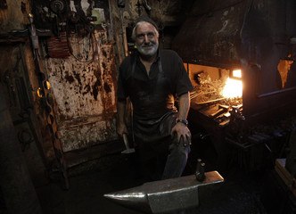 Blacksmith Alfons Neuner smiles as he stands in his blacksmith's shop in the western Austrian village of Moesern