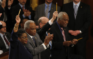 Members of the U.S. Congress hold up pencils in honor of the victims of the Paris attacks as President Barack Obama mentions the attack in his State of the Union address to a joint session of the U.S. Congress on Capitol Hill in Washington