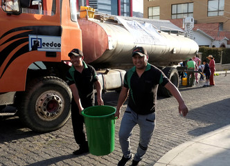 Men carry a bucket after collecting water from a water truck during a drought season in La Paz